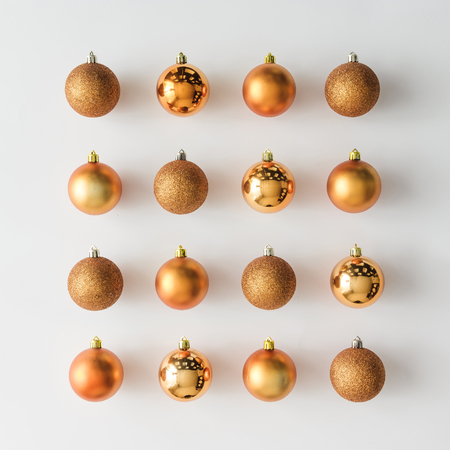 Golden Christmas baubles decoration on bright background. Flat lay. Holiday concept.