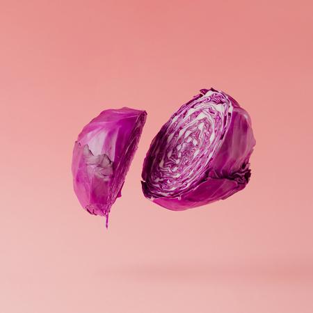 붉은 양배추 파스텔 핑크 배경에 슬라이스. 최소한의 과일 개념.