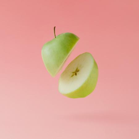 Maçã cortada em fundo rosa pastel. Conceito de frutas mínimas.