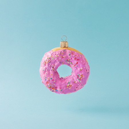 Christmas bauble decoration made of pink doughnut. Minimal New year concept.