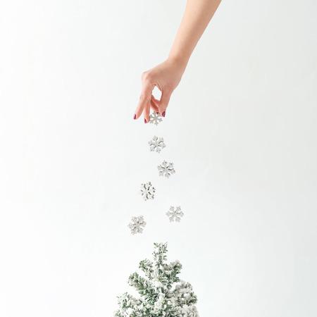 창조적 인 개념입니다. 하얀 눈송이 장식이 크리스마스 트리. 최소한의 새해 아이디어.