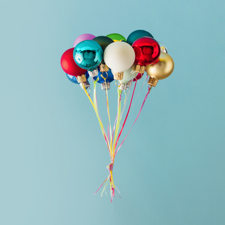 Balloons made of colorful Christmas baubles decoration on blue background. Minimal Christmas concept.
