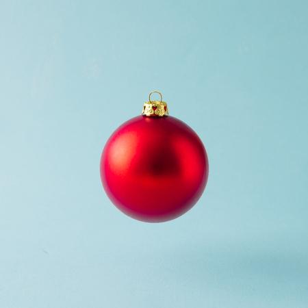 Červená vánoční cetka dekorace na modrém pozadí. Minimální vánoční koncept.
