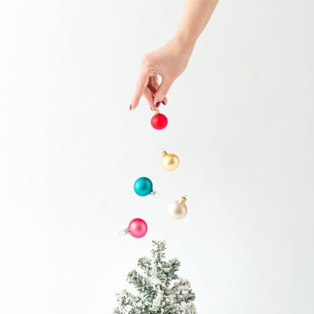 創意概念。與五顏六色的擺設裝飾的聖誕樹。最小的新的一年的想法。 版權商用圖片