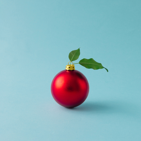 Apple kırmızı Noel bauble yaprakları ve mavi arka planda bırakır. Noel gıda konsepti. Stok Fotoğraf