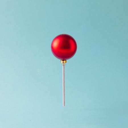 Lollipop hecho de chuchería roja de la Navidad en fondo azul. Concepto de dulces navideños. Foto de archivo