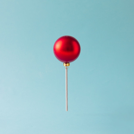 Lollipop made of red Christmas bauble on blue background. Christmas sweets concept.