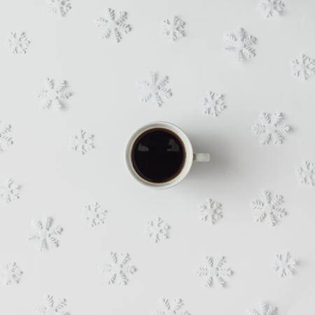 Šálek kávy se vzorem zimní sněhové vločky. Koncept minimální dovolené.