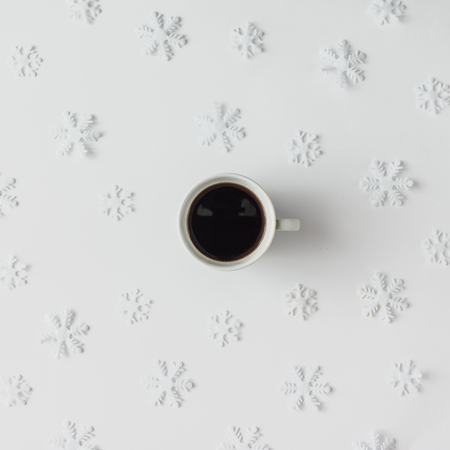 Cốc cà phê với hoa tuyết hình mẫu mùa đông. Khái niệm ngày lễ tối thiểu.