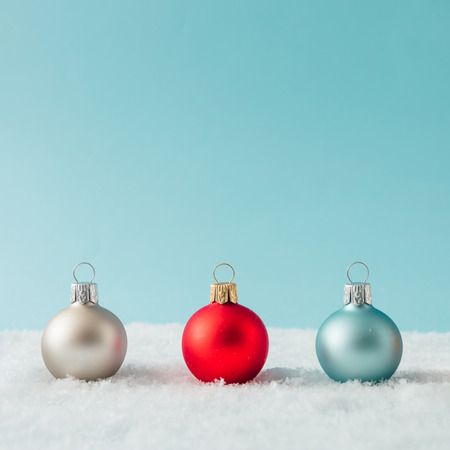 Creative layout made of Christmas bauble decoration on snow. Holiday background.