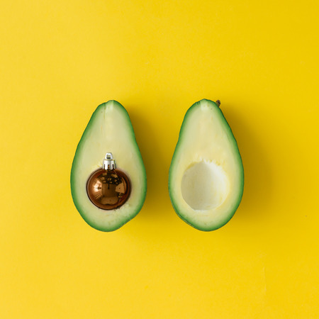 Avocado and Christmas bauble decoration on bright yellow background. Christmas concept. Flat lay.