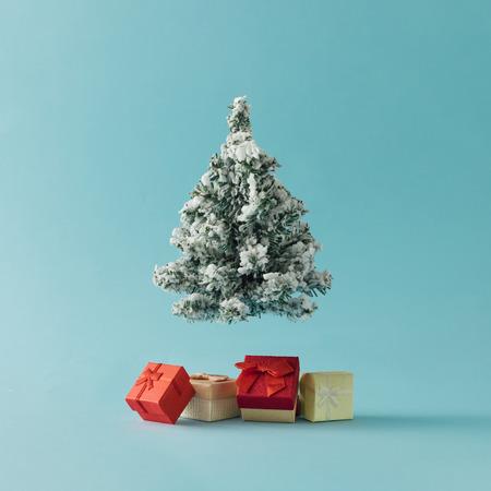 與明亮的藍色背景上的禮品盒聖誕樹。最小的假日概念。