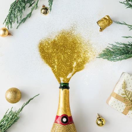 Noel yeşillikleri ve dekorasyonu ile parlak arka planda parti parıltısı ile şampanya şişesi. Parti kavramı.