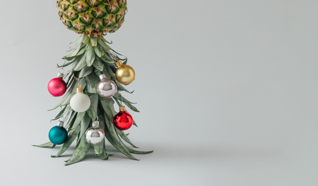 Christmas tree made of pineapple and christmas bauble decoration. Holiday concept.