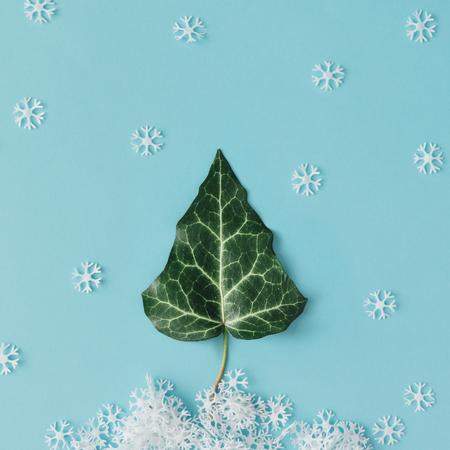 Inverno Árvore de Natal feita de folhas naturais e flocos de neve. Leito plano. Conceito de estação mínima.