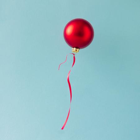 Balón z červené vánoční cetka dekorace na modrém pozadí. Minimální vánoční koncept. Reklamní fotografie