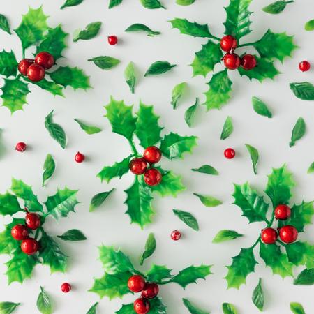 Layout criativo de Chistmas feito de planta e folhas de azevinho. Leito plano. Conceito da época natalícia