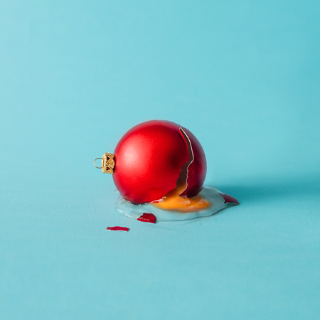 Broken Christmas bauble decoration with broken egg. Minimal concept. Stock Photo