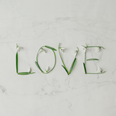 Word LOVE made of snowdrop flowers. Minimal love concept. Mothers day Flat lay.