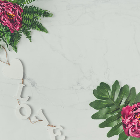 Creaative natural composition made of flowers and leaves on marble background. Flat lay. Love concept.