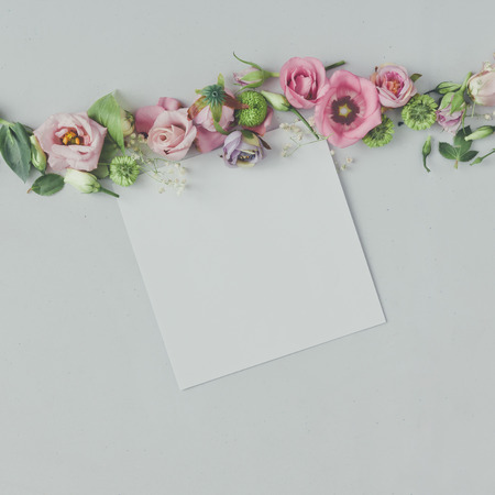 Creative natural composition made of flowers and leaves with paper card. Flat lay background. Love concept.