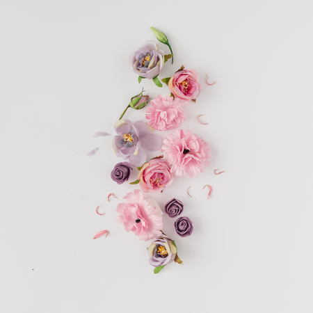 Creative layout made with pink and violet flowers on bright background. Flat lay. Spring minimal concept. Stok Fotoğraf