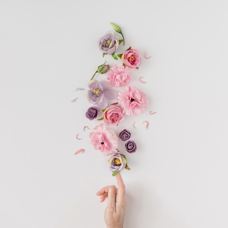 Creative layout made with pink and violet flowers on bright background. Flat lay. Spring minimal concept. Фото со стока