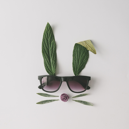 Bunny rabbit face made of natural green leaves with sunglasses on bright background. Easter minimal concept. Flat lay. Stockfoto