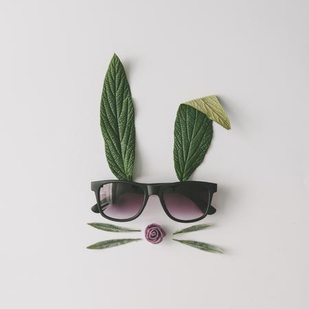 Das Häschengesicht, das vom natürlichen Grün gemacht wird, verlässt mit Sonnenbrille auf hellem Hintergrund. Ostern minimales Konzept. Flach liegen. Standard-Bild