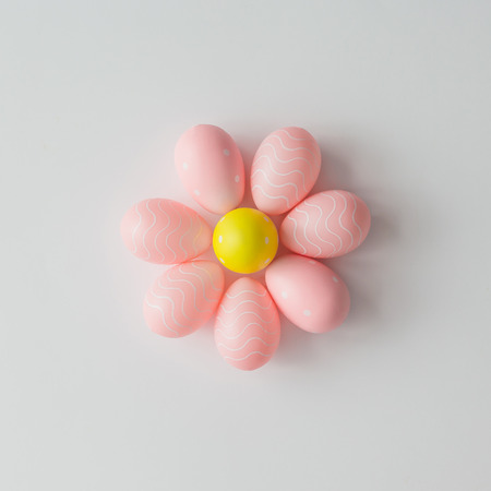 Pink flower made of Easter eggs on bright background. Creative concept. Flat lay.
