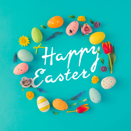 Creative Easter layout made of colorful eggs and flowers on blue background. Circle wreath flat lay concept. Stock Photo