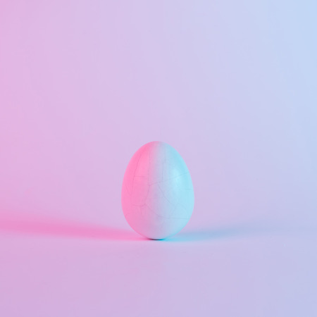 White Easter egg with colorful ultraviolet holographic neon lights. Creative concept. Stock Photo