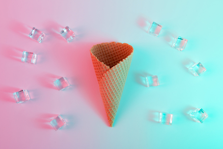 Ice cream cone with ice cubes in vibrant bold gradient holographic colors. Concept art. Minimal surrealism. Stock Photo