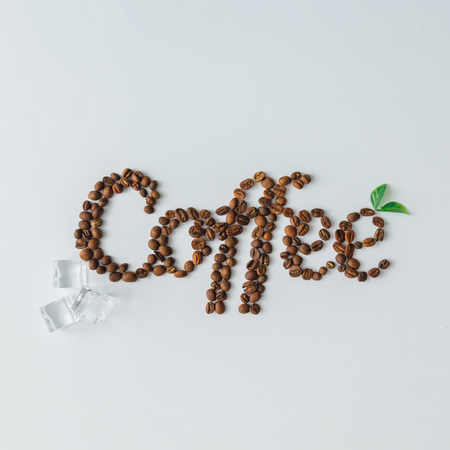 Word Coffee made of ice cubes and coffee beans on bright background. Flat lay summer drink concept. Stock Photo