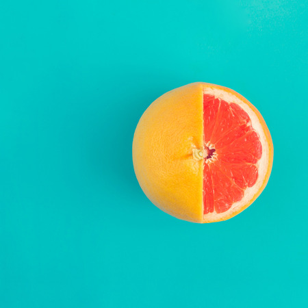 Red grapefruit on bright blue background. Minimal flat lay concept. Archivio Fotografico - 100624816