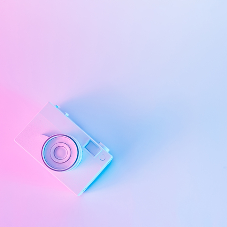 Vintage camera in vibrant bold gradient purple and blue holographic colors. Concept art. Minimal summer surrealism. Stock Photo