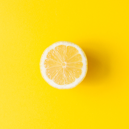 Lemon on vivid yellow background. Minimal summer concept. Flat lay.