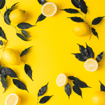 Creative summer pattern made of lemons and black leaves on yellow background. Fruit minimal concept. Flat lay. Stock Photo - 100625175