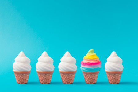 Colorful and white ice cream on pastel blue background. Creative minimal summer concept. Foto de archivo