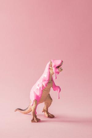 Vernice rosa che gocciola sul giocattolo del dinosauro. Concetto minimo creativo. Archivio Fotografico