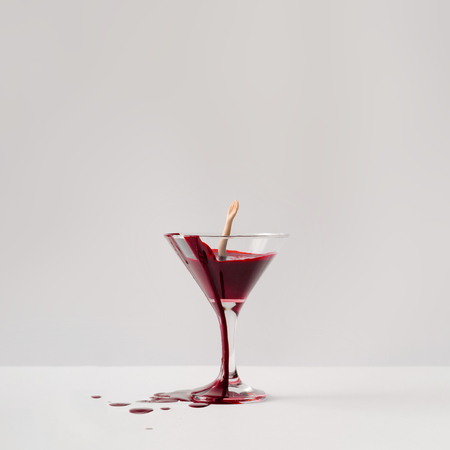 Doll hand drowning in martini glass full of blood. Minimal horror concept.