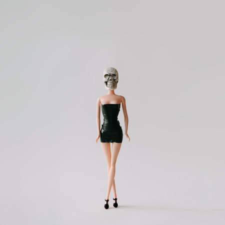 Girl doll with skull head. Minimal concept. Stock Photo