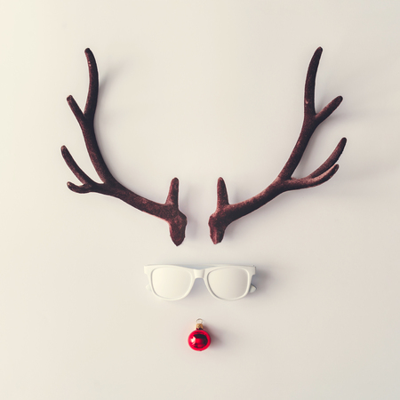 Santas reindeer made of antlers, white sunglasses and red New Year bauble decoration. Minimal winter holiday concept. Stock Photo