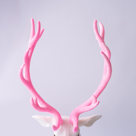 White reindeer with glitter pink antlers. Minimal New Year or Christmas background concept. Stock Photo