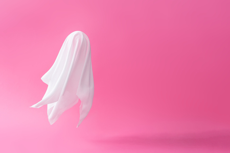 White ghost sheet costume against pastel pink background. Minimal Halloween scary concept.