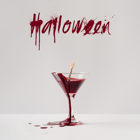Doll hand drowning in martini glass full of blood. Minimal Halloween concept.