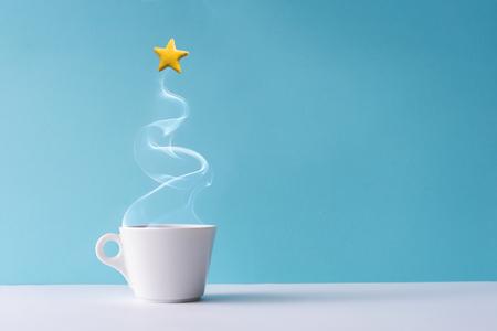 Weihnachtsbaum aus dampfendem Kaffee oder heißem Getränk mit gelbem Sternplätzchen. Winterferienkonzept. Minimaler Neujahrshintergrund. Standard-Bild - 108752217