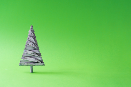 White wooden Christmas tree decoration with green background. Minimal New Year holiday concept.