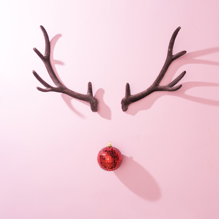 Red Christmas disco ball bauble with reindeer antlers on pink background. Minimal New year Santa concept. Flat lay. Banque d'images - 108752242