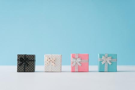 Scatole regalo colorate su sfondo blu pastello. Concetto minimo di Natale o Capodanno.